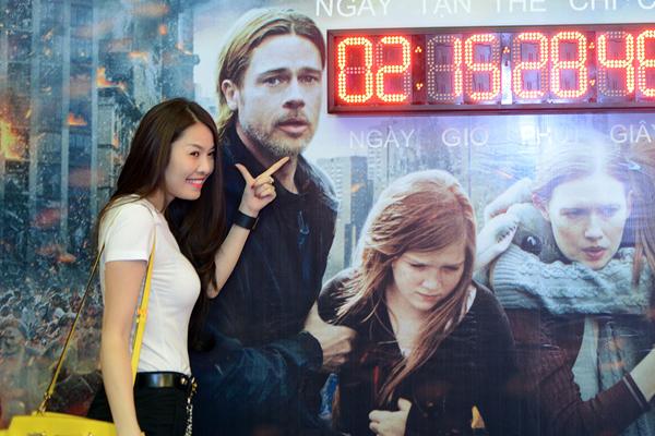Ca sĩ Quế Vân nhí nhảnh pose hình bên tấm poster có hình Brad Pitt.