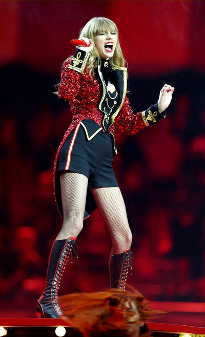 Taylor Swift holds a red mic while performing onstage during the 2012 MTV EMAs.