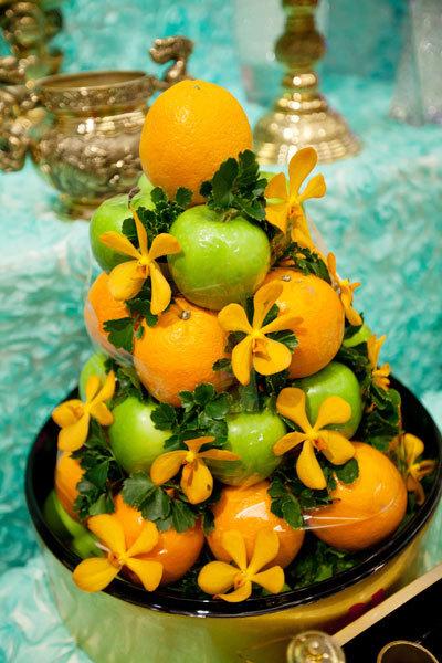 Mâm ngũ quả thông thường được cách tân thành mâm trái cây gồm cam vàng và táo xanh cùng theme màu với các trang trí.