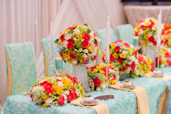 Hoa trên bàn uống nước của hai họ được chăm chút tỉ mỉ, công phu. Những bình hoa có sắc màu tươi tắn, được kết từ ba gam màu chủ đạo là xanh, vàng và cam hồng khiến không khí trẻ trung, hiện đại.