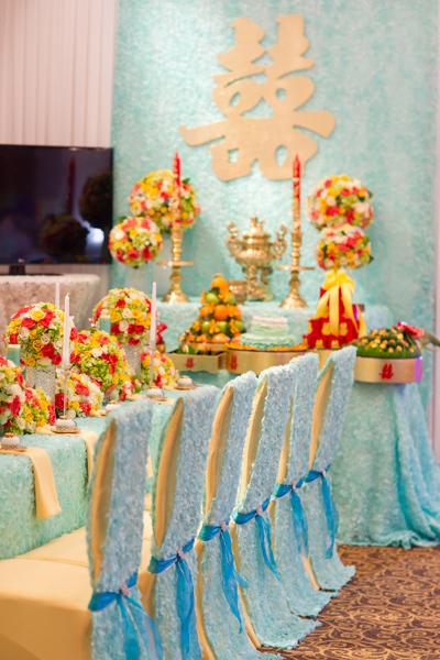 Từng chiếc áo ghế cũng được may bằng vải hoa hồng màu xanh và điểm thêm nơ ruy băng xanh đậm bắt mắt.