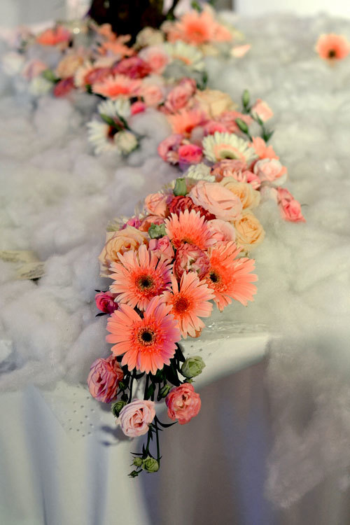"""Phần chân của """"cây"""" hoa trải dài ra bàn theo phong cách thác đổ mềm mại."""