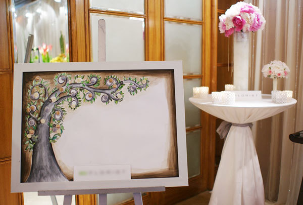 Sảnh tiệc đặt bức tranh vẽ bằng màu nước và trang trí bởi những hạt đá lấp lánh. Cô dâu chú rể có thể sử dụng bức tranh này dành cho khách mời ký tên hoặc in dấu vân tay.