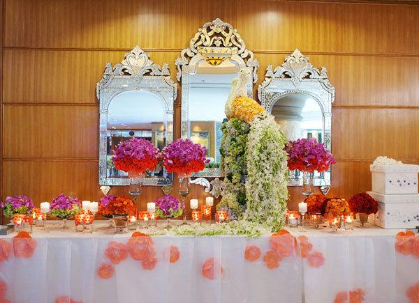Bàn đón tiếp cũng đặt một chú công nhỏ đáng yêu giữa những bình hoa rực rỡ. Sắc màu chủ đạo của bàn trưng bày