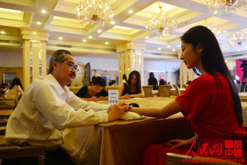 "A doctor feels the pulse on a candidates wrist to learn her health condition at the audition for the ""blind date with rich bachelor"" held in Beijing on June 30, 2013. ("
