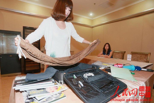 "A candidate is asked to arrange luggage for her ""spouse"" during the audition for the ""blind date with rich bachelor"" held in Beijing on June 30, 2013. She received positive comments from the marriage counselor due to her neat and orderly arrangement"