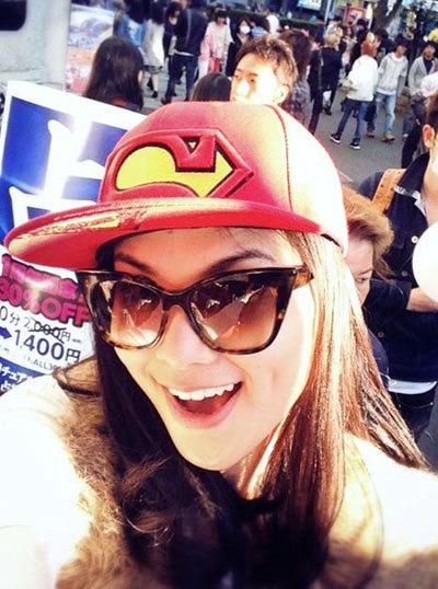 """Hoa hậu Diễm Hương tươi tắn chụp ảnh """"tự sướng"""" với chiếc mũ đỏ mang biểu tượng của chàng siêu nhân và."""
