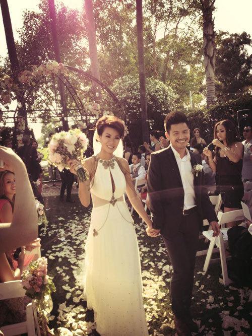 Tới giờ làm lễ, cô dâu Như Loan bước vào nơi cử hành hôn lễ trên con đường trải ngập cánh hoa hồng. Khung cảnh sân vườn đơn giản được trang trí lộng lẫy với cổng hoa lớn.