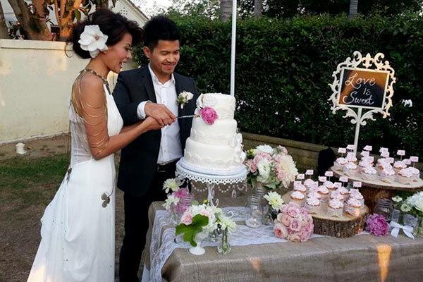 Cô dâu chú rể cùng cắt bánh cưới.