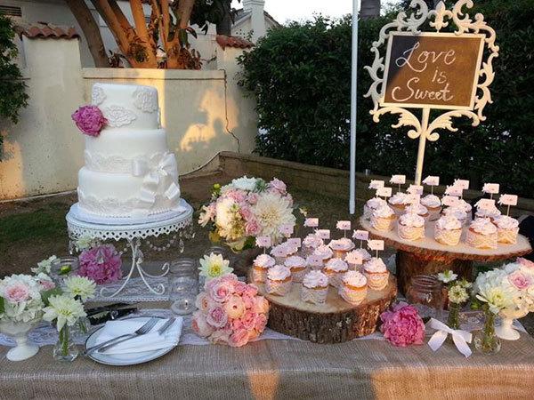 Bàn đặt bánh cưới cũng được trang trí với vải thô gai và những khúc gỗ lớn, hoàn hảo cho phong cách rustic. Ngoài ra, hoa mẫu đơn cũng hiện diện nhiều trong trang trí.