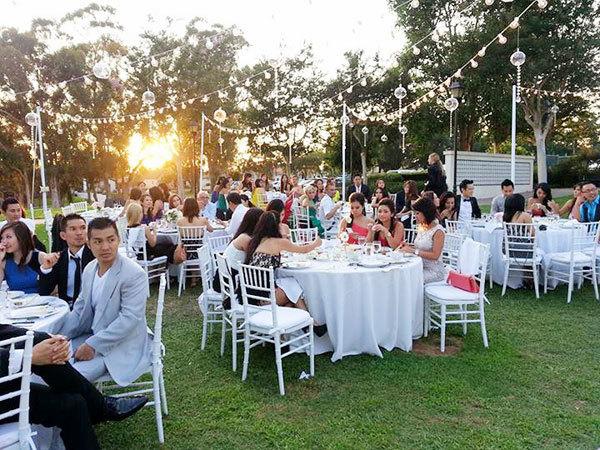 Không gian tiệc cưới đơn giản với dàn đèn treo lung linh và những bàn tiệc trắng trang nhã.