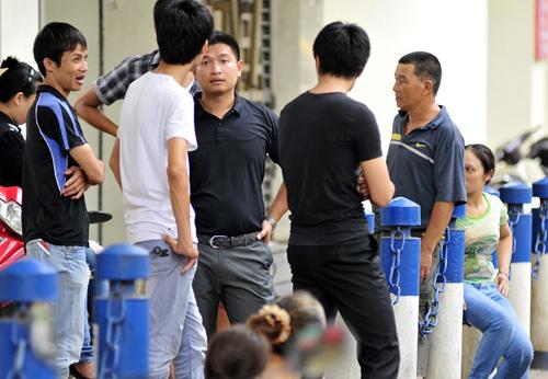 Người hâm mộ nán lại để xem xét tình hình sau khi quầy bán vé của ban tổ chức thu dọn.