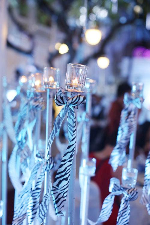 Trụ nến kế bên cổng hoa với ruy băng trắng đen ấn tượng thể hiện tông màu chủ đạo của đám cưới.