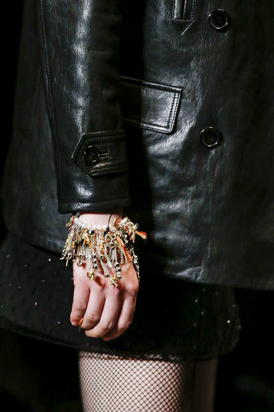 For his second ready-to-wear collection as creative director at the house Saint Laurent, Hedi Slimane looked to 1990s grunge for accessories inspiration, with diamante and spiked stockings, biker boots and leather mini-dress paired with fine pearl necklaces and layered chains and charm bracelets.