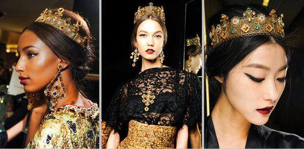 """Những mái tóc xẻ ngôi giữa, búi thấp mang phong cách thời trang những năm 1960 được """"làm điệu"""" bằng vương miện vàng độc đáo. Đây là phong cách tóc được Dolce & Gabbana lựa chọn để người mẫu trình diễn trên sân khấu."""