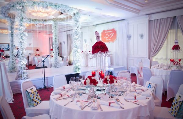 Bàn tiệc tròn được trang trí với những bình hoa thấp và cao khác nhau.