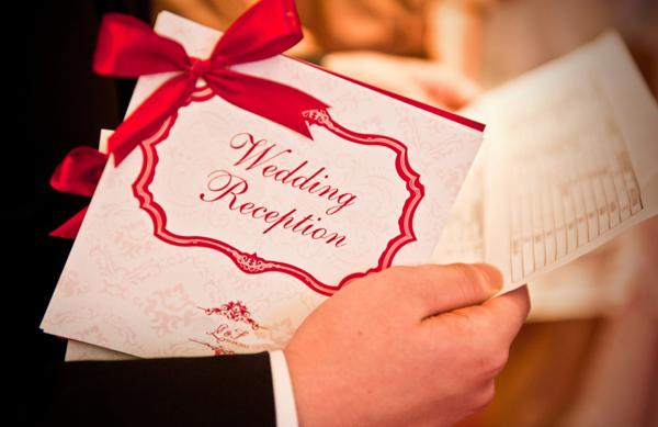 Thiệp cưới mang hai sắc màu chủ đạo với chiếc nơ ruy băng đỏ nổi bật.