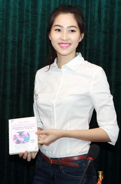 Hoa hậu trông giản dị khi mặc áo sơ mi trắng và quần jeans.