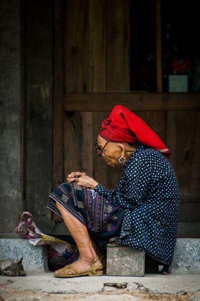 Một người phụ nữ Dao cặm cụi với những mũi chỉ. Ảnh: Trần Phong.