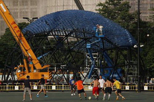 People play soccer in front of a sculpture containing 7,000 recycled plastic water bottles with LED lights, measuring 20 metres in diameter and 10 metres in height, at Hong Kong's Victoria Park September 10, 2013. The