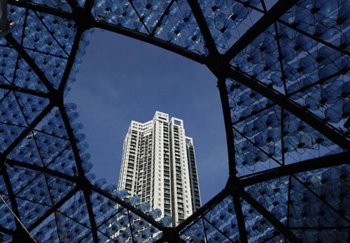 A residential tower is framed from inside a sculpture containing 7,000 recycled plastic water bottles with LED lights, measuring 20 metres in diameter and 10 metres in height, at Hong Kong's Victoria Park Sept 10, 2013. The