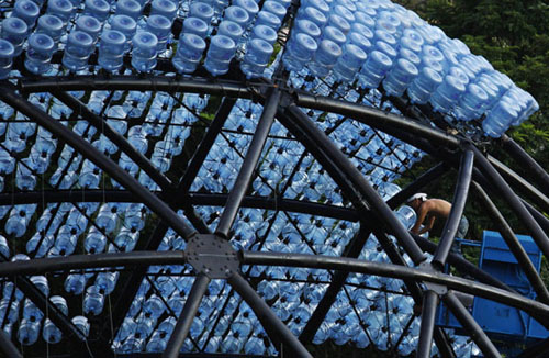 A worker builds a sculpture containing 7,000 recycled plastic water bottles with LED lights, measuring 20 metres in diameter and 10 metres in height, at Hong Kong's Victoria Park Sept 10, 2013.