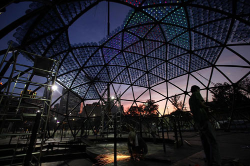 Workers build a sculpture containing 7,000 recycled plastic water bottles with LED lights, measuring 20 metres in diameter and 10 metres in height, during sunset at Hong Kong's Victoria Park Sept 10, 2013.