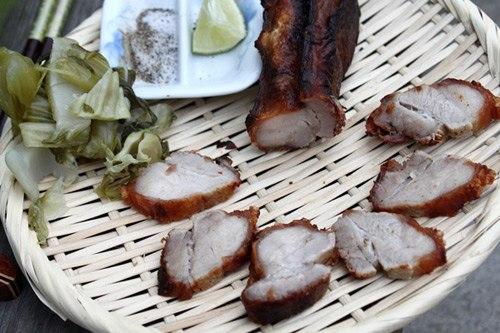 Thịt lợn quay chấm với muối tiêu chanh và ăn kèm với cải chua, cơm trắng.