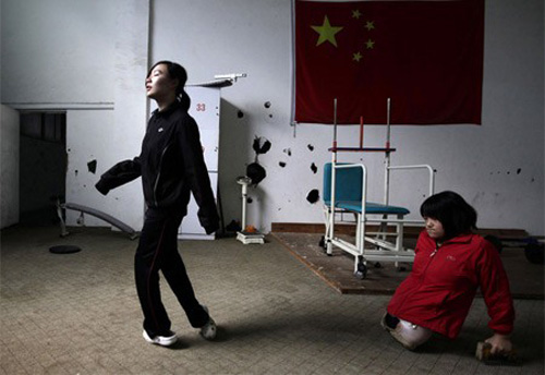 16-year-old Qian Hongyan (R) and 19-year-old Wu Qi, from the Yunzhinan Swimming Club for the handicapped, practise walking during a daily training session.  About 30 disabled athletes from the club aged 10 to 22 are training for the London 2012 Paralympic Games. The club was founded in August 2007.