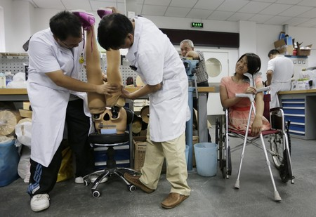 Qian Hongyan, 18, waits for her new prosthesis which are being fitted with silk stockings at China Rehabilitation Centre in Beijing, September 5, 2013.
