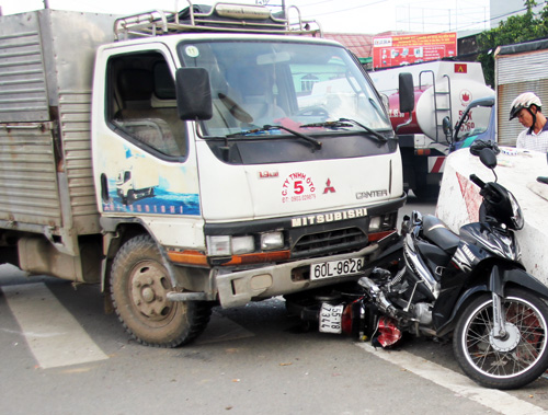 Hai xe máy của nạn nhân bị xe tải ép trước đầu xe. Ảnh: An Nhơn