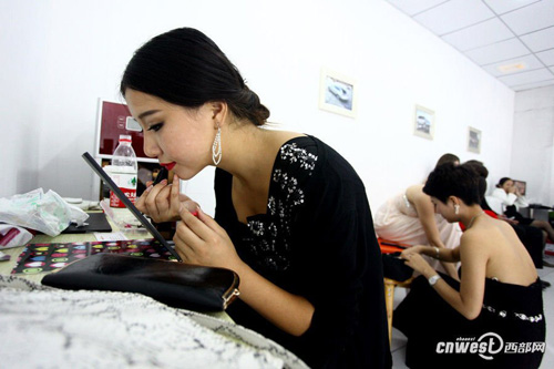 Li starts fixing her make-up as the afternoon exhibition is about to start.