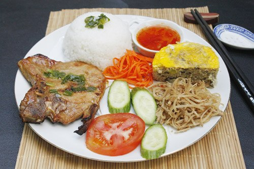 Đĩa cơm với nhiều màu sắc đẹp mắt, thịt sườn mềm, thơm ăn kèm với chả trứng, bì thịt, đồ chua và rau ăn kèm.