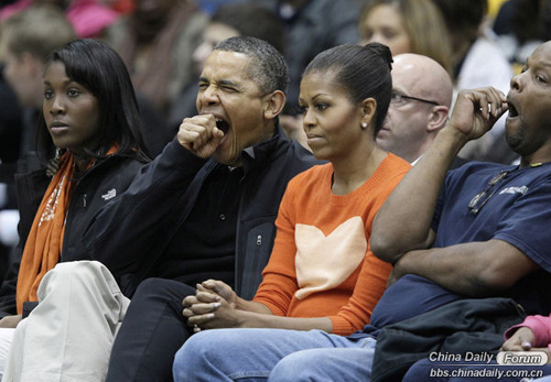 U.S. President Barack Obama yawns alongside First Lady Michelle Obama during an NCAA basketball game between Oregon State and Towson in Towson, Md., Saturday, Nov. 26, 2011.