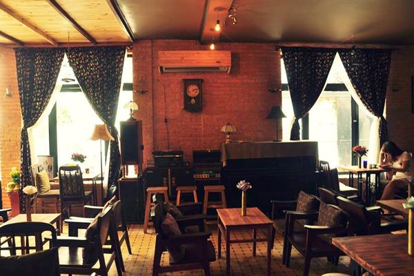 """Mang đậm nét kiến trúc miền nam Italy, quán cafe Vecchio khiến bạn liên tưởng đến những ngôi nhà nhỏ xinh và cổ điển. Đằng sau cánh cửa quán là một không gian ấm cúng và hài hòa của nghệ thuật sắp đặt mang nét hoài cổ với những chiếc loa mặt võng cũ kỹ có từ thập niên 70 của thế kỷ trước, những chiếc tivi đen trắng, máy đánh chữ, bàn ủi con gà... Ngoài những bản nhạc Italy nhẹ nhàng, hàng đêm quán còn thu hút thực khách với chương trình ca nhạc theo phong cách Acoustic. Thực khách sẽ được """"phiêu"""" theo những ca khúc bất hủ bằng tiếng Anh, Việt và Italy như Yesterday, Top of the world, Saving all my love for you hay những tình khúc Quốc Bảo, Phạm Duy, Ngô Thụy Miên& dưới âm thanh du dương của piano, violin và guitar."""