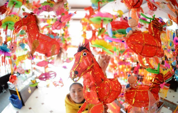 A woman selects horse-shaped lanterns in Yangzhou, east China's Jiangsu Province, Feb. 10, 2014. Many people purchase festival lanterns to celebrate Chinese Lunar New Year of Horse. (Xinhua/Meng Delong)