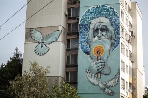 """Câu chuyện về người đàn ông Bulgaria tuyệt vời đã được cả thế giới biết đến và ca ngợi. Để bày tỏ tấm lòng ngưỡng mộ và yêu mến của người dân dành cho vị """"thánh ăn xin"""", họa sĩ đường phố Ernaste Nasimo từ Creatures Urban đã vẽ nên bức chân dung của cụ Dobri tại khu nhà Hadji Dimitar ở Sofia."""