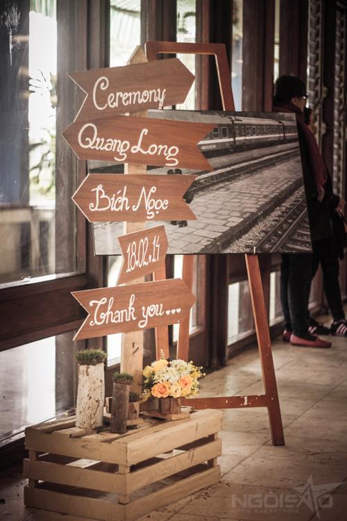 Bảng đón khách được ghép từnhững tấm gỗ đơn giản nhưng được điểm xuyết bằngsắc hoa vàng và cỏ xanh đầy sức sống.