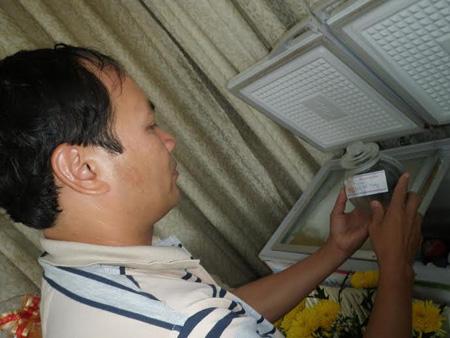Linh mục Nguyễn Văn Tịch đang nâng niu một lọ đựng thai nhi được lấy ra từ tủ đông.
