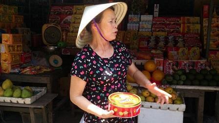 bà Nguyễn Thị Tỵ  và chiếc hộp đựng thẻ điện thoại bị đánh cắp.