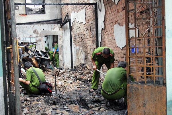 Cảnh sát khám nghiệm căn nhà bị cháy rụi. Ảnh: Châu Thành