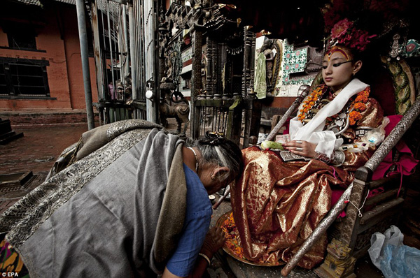 Kumaris are chosen as infants in Nepal to become living goddesses, who are then worshipped by thousands of Hindus and Buddhists until they reach puberty.  Here, one Kumari, Samita Bajracharya, is worshipped by a devotee at a festival during one of her nine public appearances throughout the year  Read more: http://www.dailymail.co.uk/news/article-2654161/The-real-life-goddesses-feet-touch-ground-Incredible-images-incarnated-Nepalese-virgins-live-temples-school-forbidden-walking-reach-puberty.html#ixzz34JxzRawY  Follow us: @MailOnline on Twitter | DailyMail on Facebook