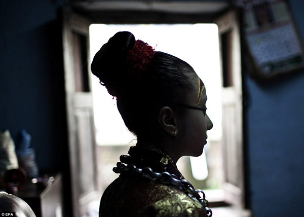 The goddesses live in temples and other enclosed areas and cannot be seen in public, apart from during ceremonies and festivities. Here, Kumari Samita Bajracharya prepares to take part in a procession at Kumari Ghar in Patan, Nepal. She appears outside of her residence during different jatras nine times a year