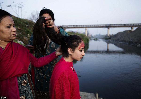 Samita Bajracharya looks ahead as her mother loosens her hair, to mark the end of her 12-day 'Gufa' ritual at Bagmati river in Patan, Nepal