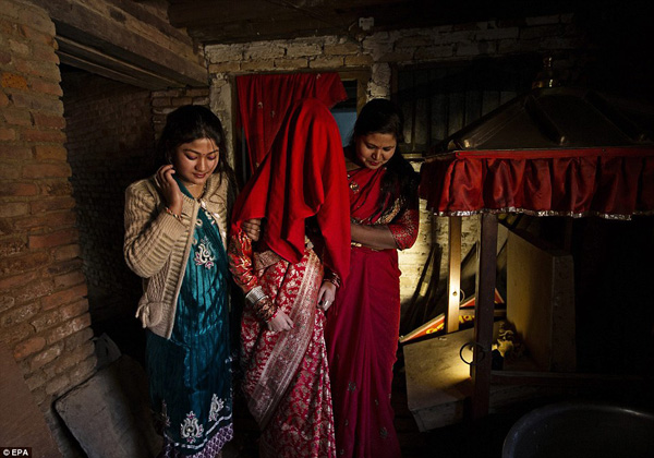 Purna Shova Bajracharya and her daughter cover Samita Bajracharya's face with a cloth as she is brought outside wearing a traditional wedding dress to worship the Sun during the 'Gufa' ceremony