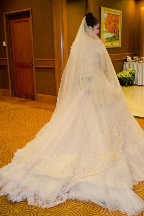 Côdâu của Đăng Khôi diện chiếc váy của nhà thiết kế Anh Thư. Chiếc váy có gam màu ngà với phần thân đính hoa ánhvàng kim tuyến, chân váy xòe bồng bềnh theo kiểu dáng công chúa. Dáng váy xòe có phần đuôi dài được trang trí bằng hoa văn ren baroque - đặc trưng trong các thiết kế của Anh Thư.