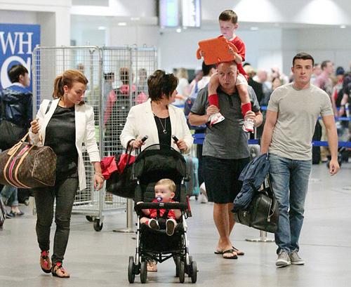 Coleen cùng bố mẹ đẻ, em trai và hai cậu nhóc Kai, Klay tại sân bay Manchester hôm 16/6.