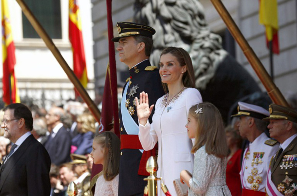 Spanish Prime Minister Mariano Rajoy (L) Spain's King Felipe VI (C), Spain's Queen Letizia Spanish Crown Princess of Asturias Leonor (2L) and Spanish Princess Sofia review troops at the Congress of Deputies, Spain's lower House in Madrid on June 19, 2014 after a swearing in ceremony of Spain's new King before both houses of parliament.