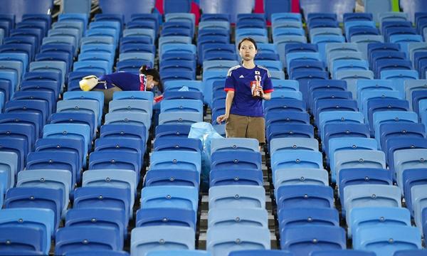 Khán đài sau trận vắng lặng, chỉ còn một số fan Nhật ở lại tự nguyện thu gom giấy rác.