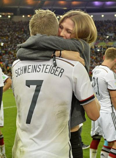 Tiền vệ Schweinsteiger được bạn gái Sarah Brandner chúc mừng bằng cái ôm thật chặt và nụ cười tươi.